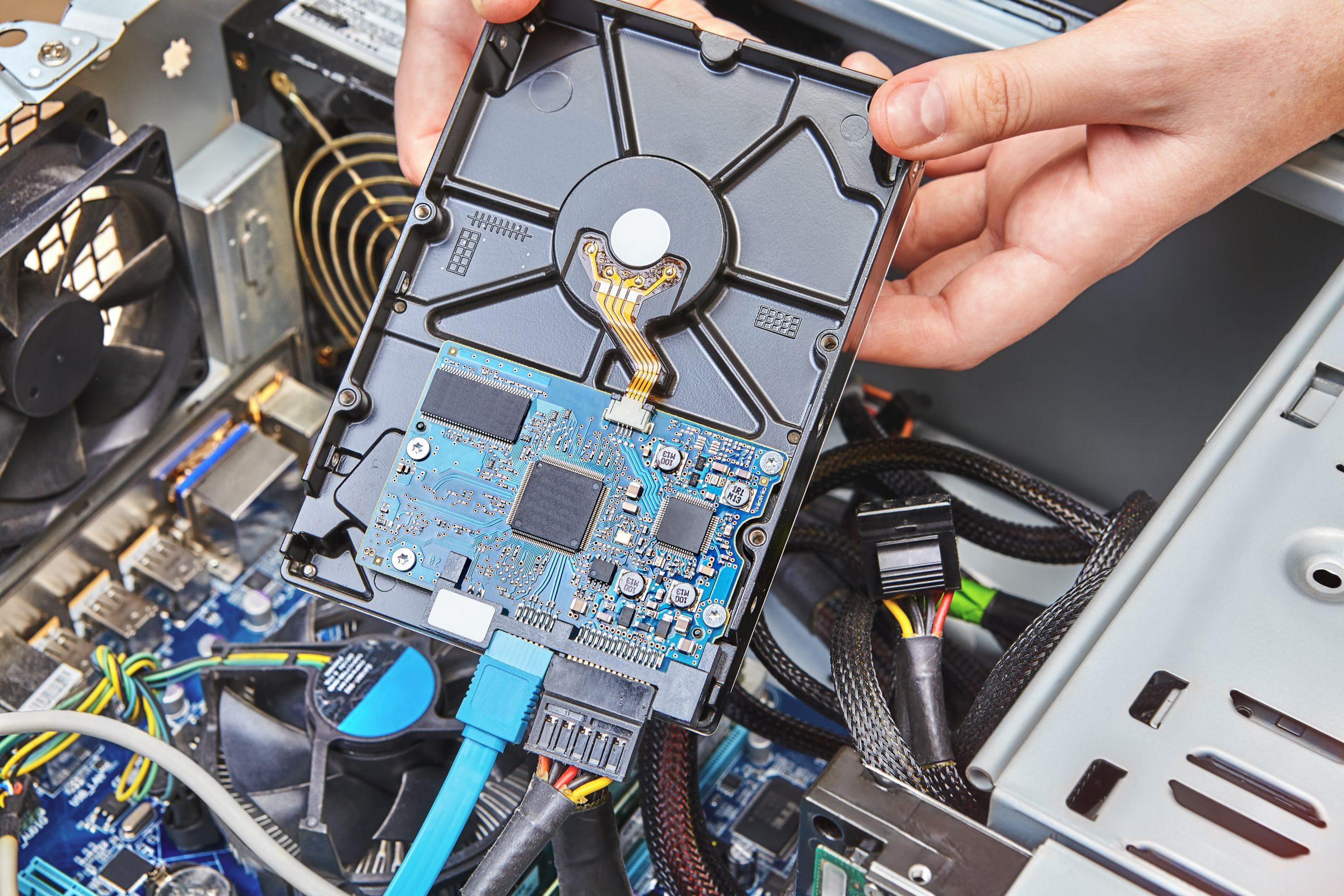 Repairman is installing an internal hard drive of the desktop PC, close up.