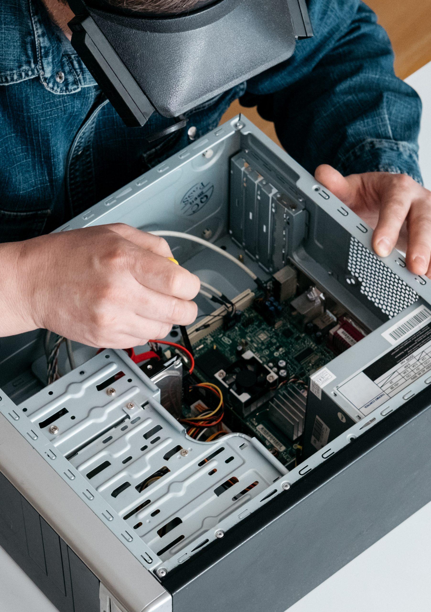 Personal computer repairing service, professional technician with magnifying glasses and screwdriver repairing broken pc desktop computer in workshop.
